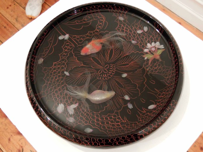 A pair of goldfish and cherry blossom petals in lacquer tray